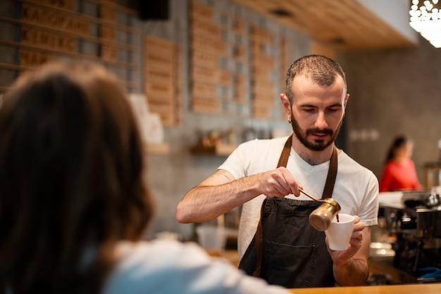 Homem de avental, derramando café na xícara para o cliente