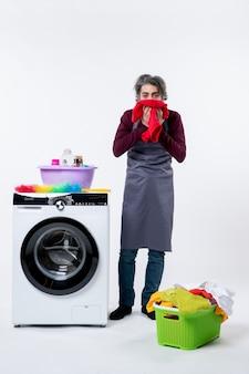 Homem de avental enxugando o rosto com uma toalha em pé perto da máquina de lavar na parede branca