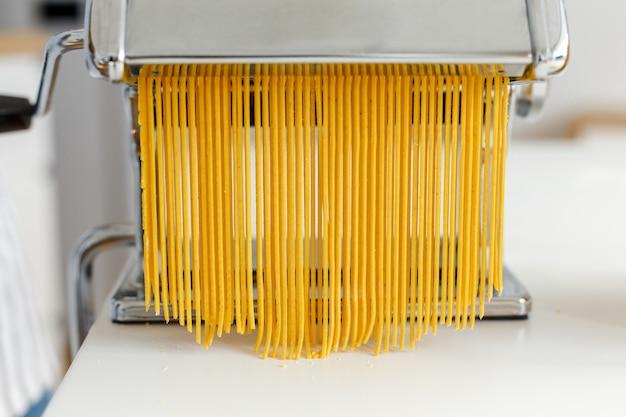 Homem de avental fazendo espaguete com cortador de macarrão closeup macarrão cozinhando em casa