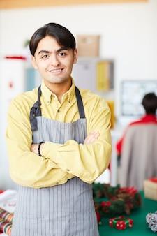 Homem de avental posando com os braços cruzados