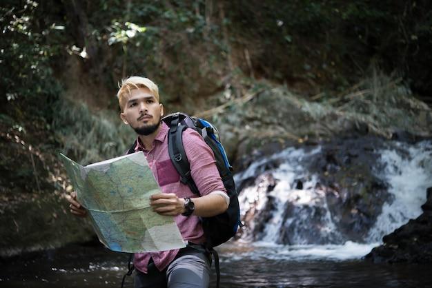 Homem de aventura que observa o mapa no caminho da montanha para encontrar o caminho certo.