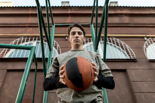 Homem de baixa visão segurando uma bola de basquete