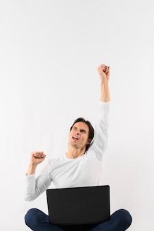 Homem de baixo ângulo com laptop feliz