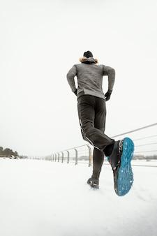 Homem de baixo ângulo correndo ao ar livre