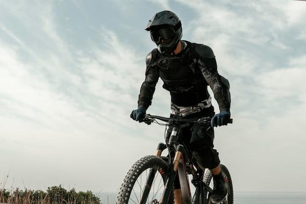 Homem de baixo ângulo em equipamento de mountain bike