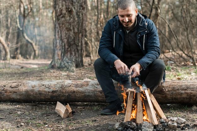 Homem de baixo ângulo fazendo fogueira