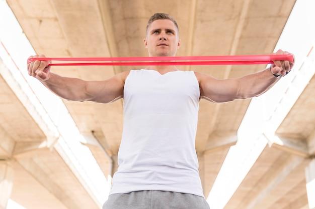 Homem de baixo ângulo, malhando com faixa vermelha de alongamento