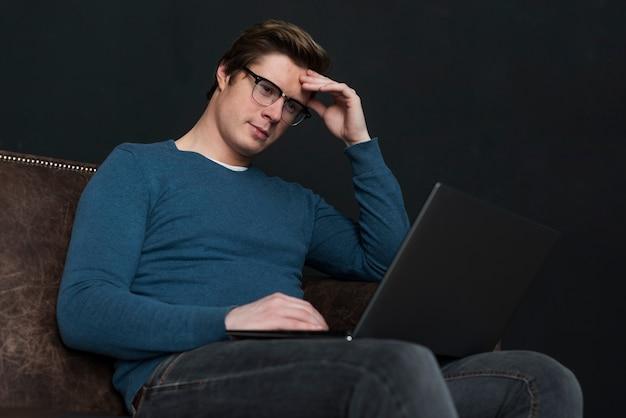 Homem de baixo ângulo, olhando em seu laptop