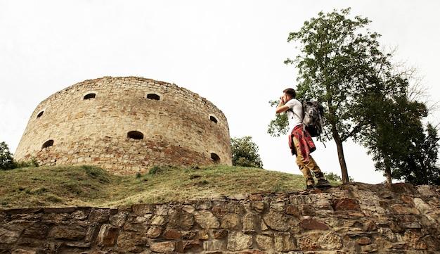 Homem de baixo ângulo, tirando fotos do castelo