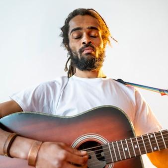 Homem de baixo ângulo tocando guitarra dentro de casa