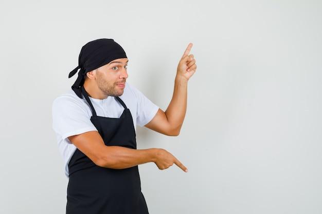 Homem de baker apontando os dedos para cima e para baixo na camiseta