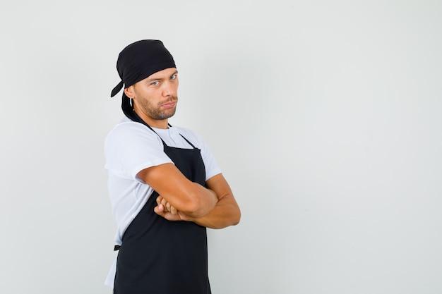 Homem de baker em pé com os braços cruzados em t-shirt, avental e olhando sério.