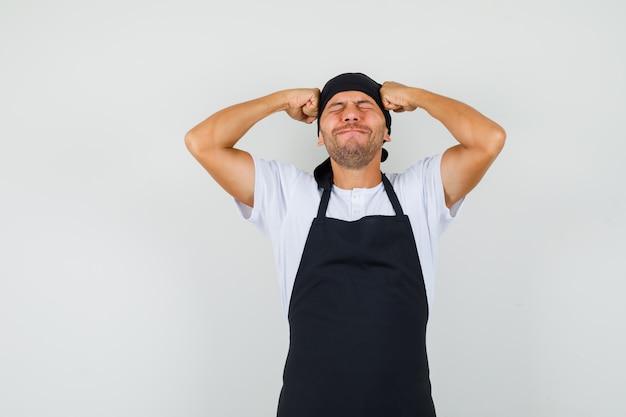 Homem de baker segurando os punhos na cabeça em uma camiseta