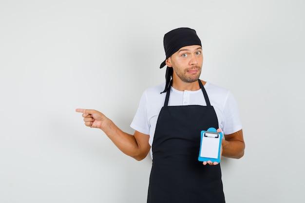 Homem de baker segurando uma mini prancheta, apontando para o lado na camiseta