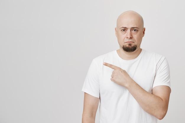 Homem de barba careca decepcionado e sombrio apontando o dedo para a esquerda chateado