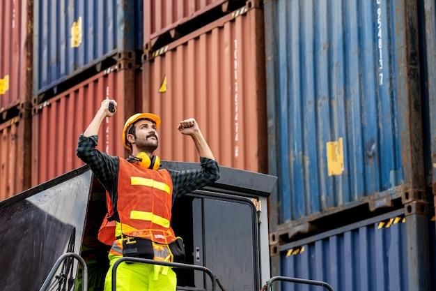 Homem de barba de engenheiro de pé com um capacete amarelo para controlar o carregamento