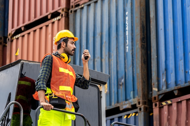 Homem de barba de engenheiro em pé com ware um capacete amarelo para controlar o carregamento e verificar a qualidade dos contêineres do navio de carga de carga para importação e exportação no estaleiro ou porto