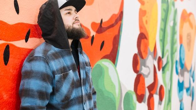 Homem de barba em frente a parede grafite colorido