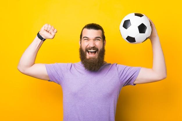 Homem de barba espantado, gritando e comemorando a vitória, torcedor apoiando o time favorito e segurando uma bola de futebol