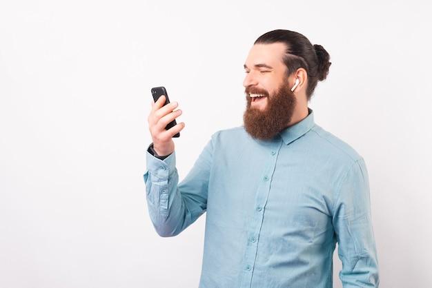 Homem de barba feliz está usando seu telefone e fones de ouvido.