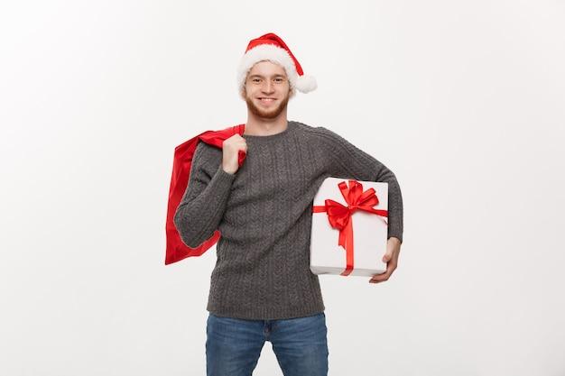 Homem de barba feliz jovem segurando uma bolsa de papai noel e um presente branco.
