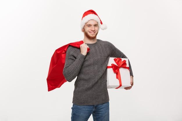 Homem de barba feliz jovem segurando uma bolsa de papai noel e um presente branco. Foto gratuita