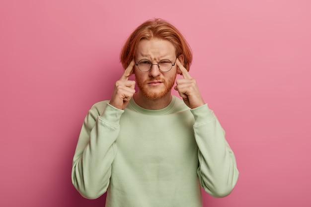 Homem de barba intensa tocando as têmporas com os dois dedos indicadores
