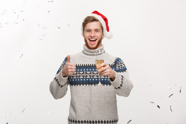 Homem de barba jovem e feliz, caucasiano, segurando uma taça de champanhe com confete