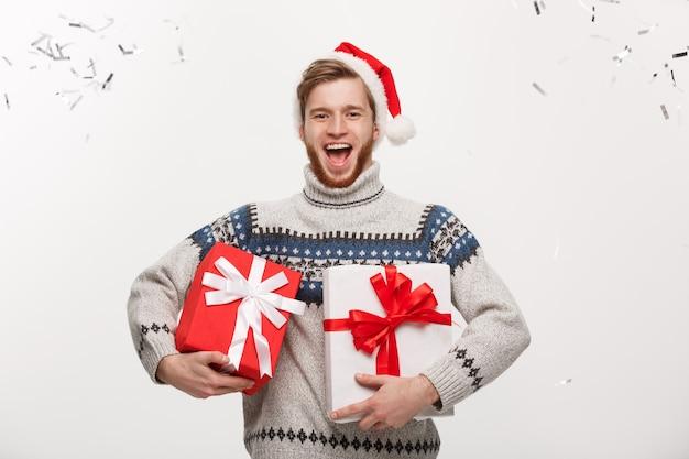 Homem de barba jovem e feliz segurando uma caixa de presente com confete