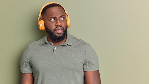 Homem de barba preta intrigado parece indignado ao lado usa fones de ouvido sem fio e escuta poses de áudio em uma camiseta casual isolada na parede do estúdio com espaço em branco