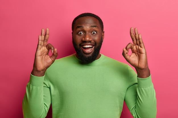 Homem de barba preta positivo encoraja amigo que tudo vai ficar bem, mostra-se bem, faz gesto de aprovação, sorri amplamente