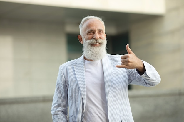 Homem de barba sênior fazendo sinal de telefone