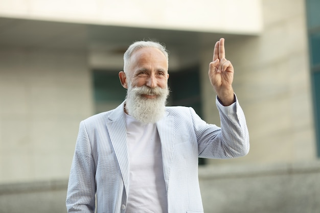 Homem de barba sênior levantando os dedos ao ar livre