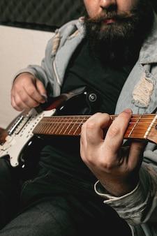 Homem de barba tocando guitarra elétrica