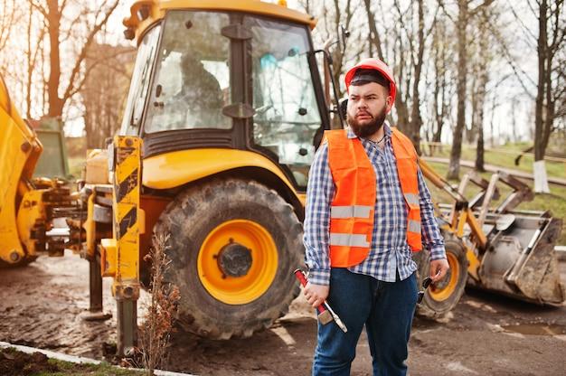 Homem de barba trabalhador terno trabalhador da construção civil no capacete de segurança laranja, contra trator com chave ajustável na mão.