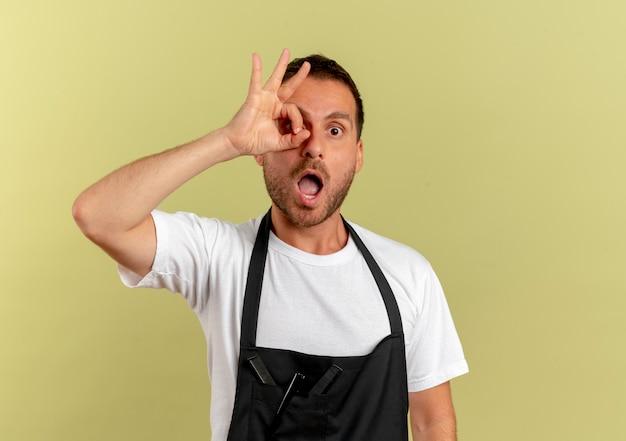 Homem de barbeiro com avental olhando para a frente fazendo sinal de ok olhando através deste sinal em pé sobre a parede de luz