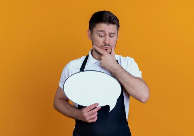 Homem de barbeiro com avental segurando um cartaz de bolha do discurso em branco olhando para ele com a mão no queixo pensando em pé sobre um fundo laranja