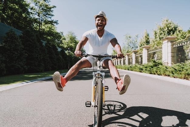Homem de bicicleta abriu as pernas em direções diferentes.