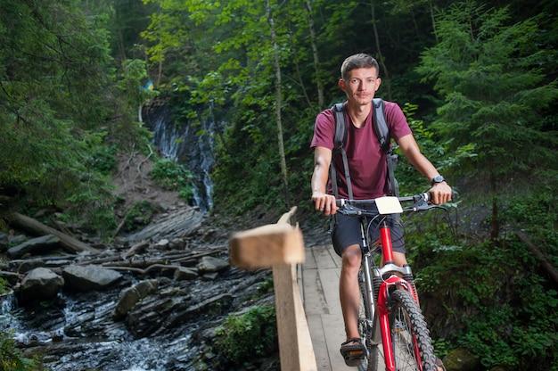 Homem de bicicleta na floresta