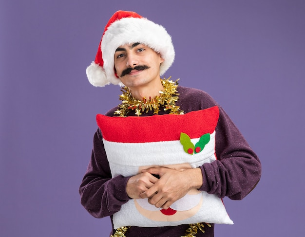 Homem de bigode feliz usando chapéu de papai noel com enfeites de natal segurando uma almofada de natal com um sorriso no rosto em pé sobre a parede roxa