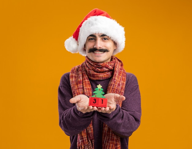 Homem de bigode feliz usando chapéu de papai noel com lenço quente em volta do pescoço mostrando cubos de brinquedo com a data de ano novo sorrindo alegremente em pé sobre a parede laranja