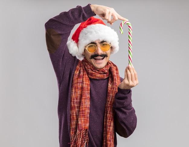 Homem de bigode feliz usando chapéu de papai noel de natal e óculos amarelos com um lenço quente em volta do pescoço segurando uma bengala de doces e sorrindo alegremente em pé sobre uma parede branca