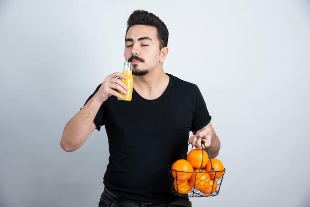 Homem de bigode segurando uma garrafa de vidro de suco com uma cesta metálica cheia de frutas de laranja.