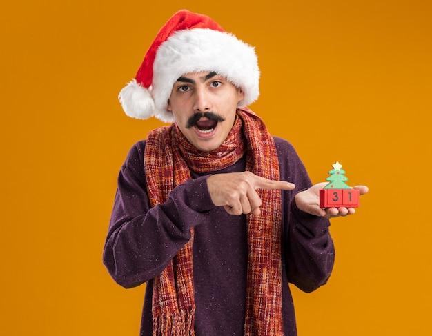 Homem de bigode surpreso usando chapéu de papai noel de natal com um lenço quente em volta do pescoço segurando cubos de brinquedo com a data de ano novo apontando com o dedo indicador para cubos em cima da parede laranja