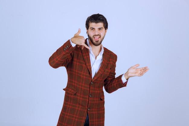 Homem de blazer marrom flertando e fazendo sinal de chamada.