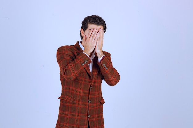 Homem de blazer marrom parece confuso e tenta se explicar.