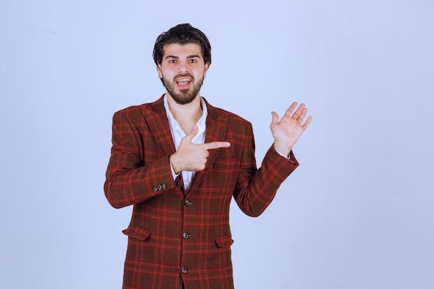 Homem de blazer xadrez apontando para algo à direita e falando sobre isso.
