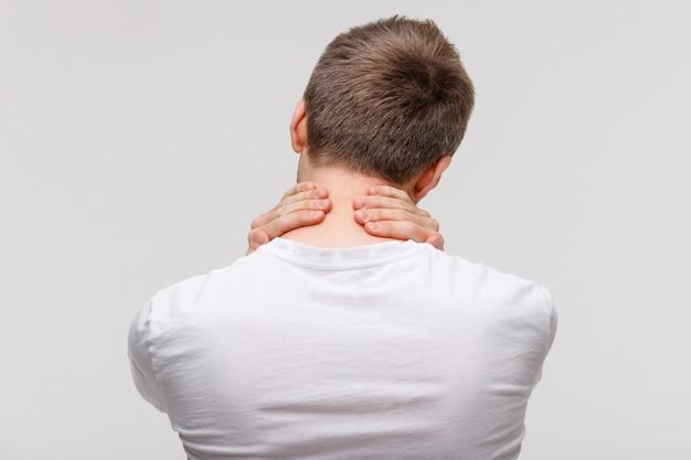 Homem de blusa branca, tocando sua dor no pescoço e nas costas