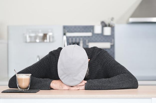 Homem de boné com a cabeça baixa nas mãos sobre uma mesa com um copo de café e leite
