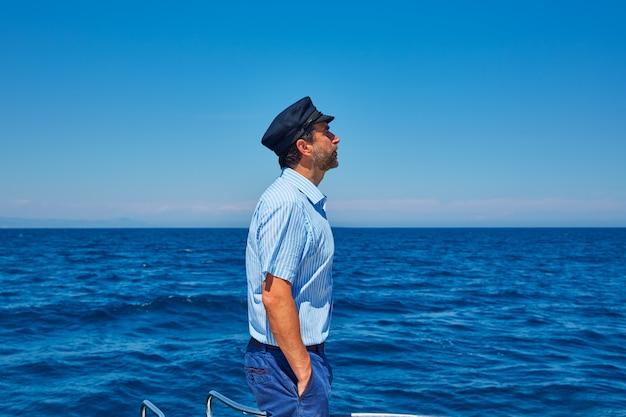 Homem de boné de marinheiro de barba navegando mar oceano em um barco